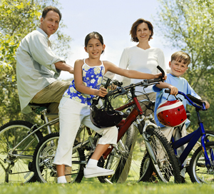 A man, woman, and 2 children out for a ride on their bikes in the park.