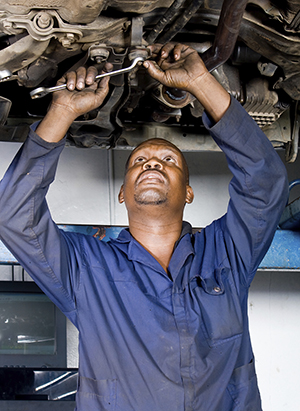 Male mechanic working under lifted car.