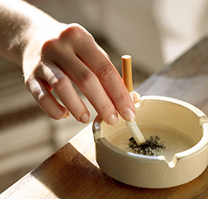 Woman's hand putting out a cigarette in an ash tray.