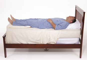 Man lying on back in bed with pillows under legs.